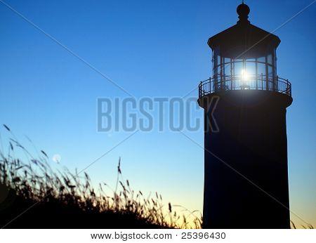 Light Shining In The North Head Lighthouse On The Washington Coast At Sunset