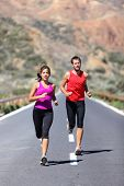 Couple running. Two runners training for marathon run outdoors on road in beautiful landscape. Man C