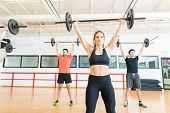 Focused Female Weightlifter Exercising With Barbell In Health Club poster