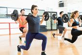 Female Weightlifter Lifting Barbell While Doing Lunges With Friends In Health Club poster