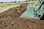 Close Up Of A Tractor Bucket Scooping Up Dirt From A Dirt Pile poster