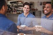 Three male friends laughing over coffee at a coffee shop poster