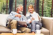 Senior Couple Relax Talking And Reading Newspaper Together On Sofa In Living Room At Home.retirement poster