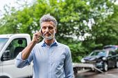 Mature Man Making A Phone Call After A Car Accident. Copy Space. poster