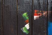 On A Wooden Background, Which Is Painted With Black Paint Painted With Different Colors Of Paint Sme poster