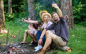 Friends Near Bonfire Enjoy Vacation And Roasted Food. Tourists Sit Log Near Bonfire Taking Selfie Ph poster