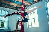 Graceful Gymnast Performing Aerial Exercise With Red Fabrics On Blue Old Loft Background. Young Teen poster