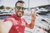 Young Happy Smiling Man In Glasses In Yacht Club. Guy In Red Shirt. Businessman In Sunglasses. Hands poster