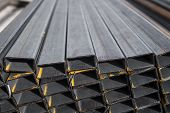 Square Flat-rolled Pipe Metal Profile In Packs At The Warehouse Of Metal Products. Weathered Metals  poster