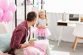 Father Looking To Daughter In Pink Tutu Skirt poster