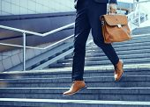 Businessman Making Steps Down Stairs. Cropped Shot Of Man Wearing Elegant Suit And Shoes Walking Dow poster