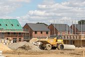 Construction Industry. Building New Homes On A New Housing Estate. Unfinished Buildings On A Buildin poster
