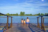 Children Sitting On Pier. Three Children Of Different Age - Teenager Boy, Elementary Age Boy And Pre poster