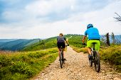Cycling, mountain biker couple on cycle trail in autumn Mountains. Man and woman cycling MTB flow tr poster
