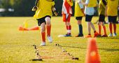 Young Athletes Training With Football Equipment. Football Speed Training For Kids. Young Footballer  poster