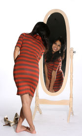 image of tight dress  - Attractive young woman in a tight dress looking at herself in a mirror Latina black cute Hispanic hair dark long female girl hair isolated long model pose pretty beige slim smile teen teenage teenager top woman young attractive expressions eyes face happ - JPG