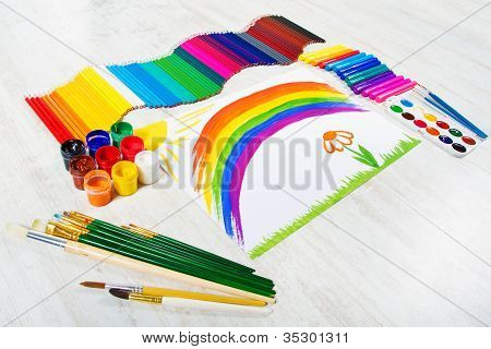 Painting Tools Set And Child Drawing Picture Of Rainbow. Creativity Concept.