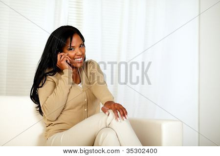 Young Woman Smiling At You While Speaking On Phone