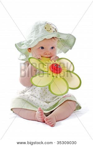 Adorable Baby Girl In Pretty Dress And Sun Hat Sits And Puts Big Toy Flower In Her Mouth