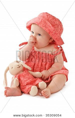 Adorable Baby Girl In Pink Dress And Sun Hat Sucks Her Thumb And Cuddles With Matching Toy Rabbit
