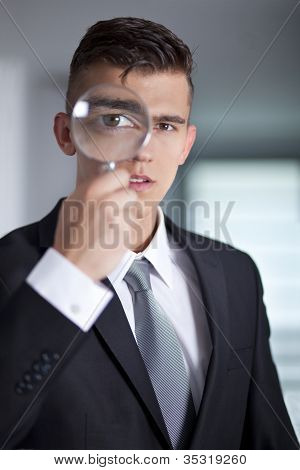 Young Businessman In A Suit Looking Through A Magnifying Glass