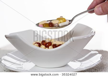 Spoon Of Vitamins Over Bowl Of Tablets