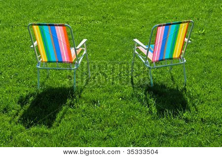 Two Colorful Chairs Standing On Grass