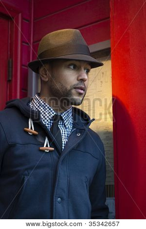 Young Black Man With Fedora In Red Doorway