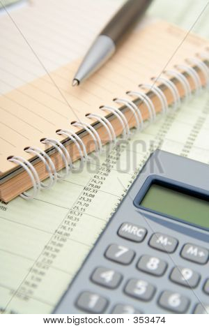 Calculator, Pen And Notebook On Financial Paper