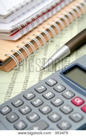 Calculator, Pen And Notebooks On Financial Paper