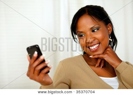Smiling Female Sending A Message By The Cellphone