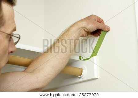 Man Peeling Painter's Tape