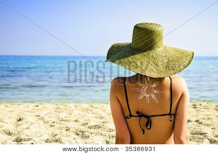 Woman On Beach With Sun Symbol On Her Back