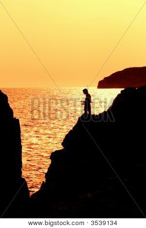 Child Fishing In Sea At Sunset