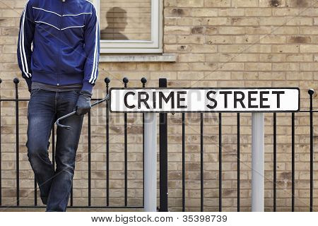 Burglar Standing On Street With Crowbar And Leather Gloves