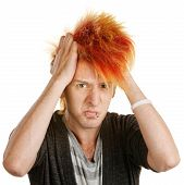 stock photo of mohawk  - Frustrated male teenager in mohawk pulling his hair - JPG