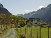 stock photo of hayfield  - landscape in norway with house in deep valley - JPG
