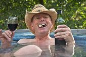 Middle Aged Man In Cowboy Hat Sitting In Hot Tub With Wine.