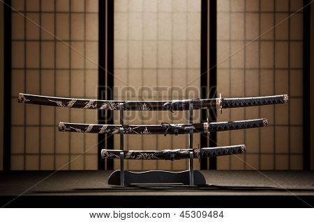 Katana, Wakizashi And Tanto On Stand In A Room