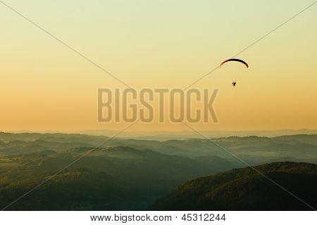 Moto Paraglider Above The Landscape In Sunset