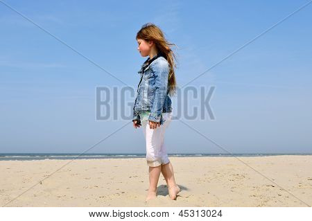 child standing on the beach with jeans jacket and white pants