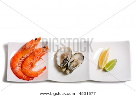 Plate With Prawns Oysters Lemon And Lime Isolated On A White Background