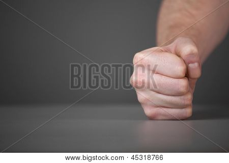 Male fist on the table.
