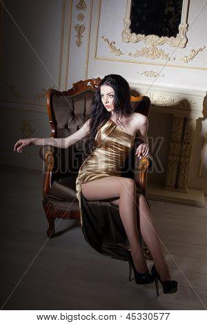 Girl In Golden Dress Sitting In An Elegant Chair