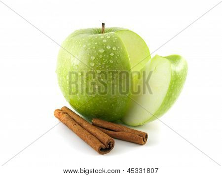 Isolated sliced green apple with cinnamon pods.