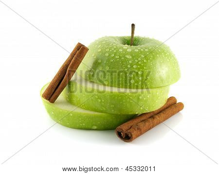 Isolated wet green apple slices with cinnamon pods