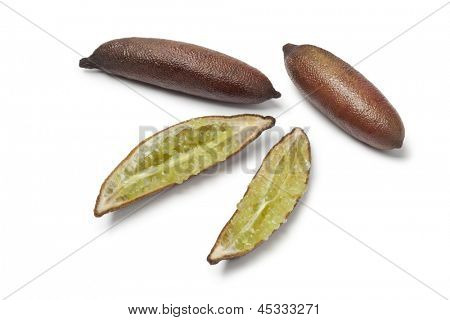 Whole and half finger limes on white background
