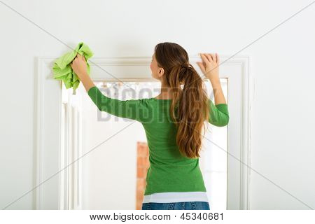 Young woman cleaning at home, she has a cleaning day and using a duster or dust cloth