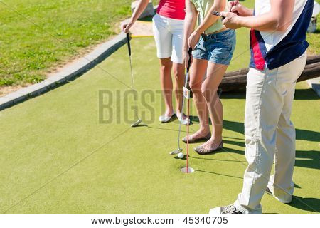 People, man and women, playing miniature golf on a beautiful summer day