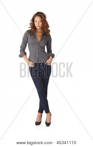 Pretty girl standing legs crossed over white background. Full length.